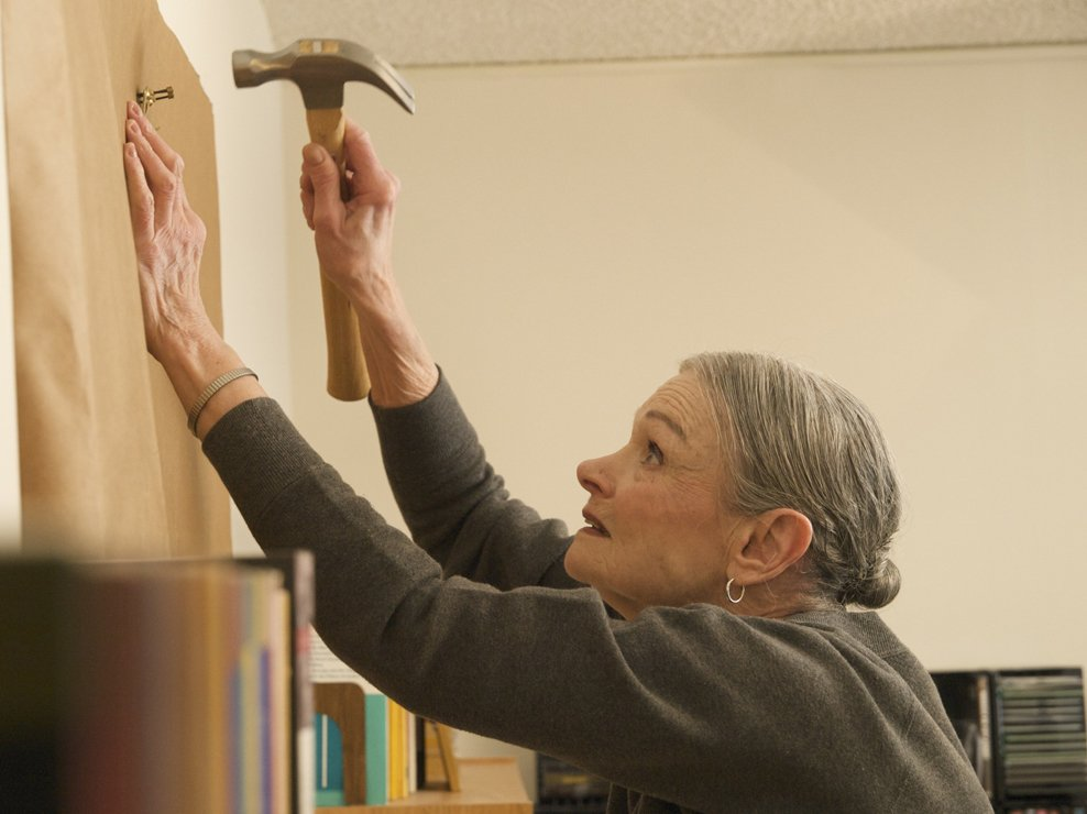 Lila, an interior decorator, shows good form in sinking a hook for Buddy's artwork. As a mother-and-son team, they worked together to organize and decorate his apartment.